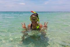 使假期戴着废气管水肺面具的乐趣妇女靠岸做一张愚蠢的面孔,当游泳在海洋水中时 特写镜头 免版税库存图片