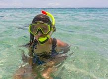 使假期戴着废气管水肺面具的乐趣妇女靠岸做一张愚蠢的面孔,当游泳在海洋水中时 特写镜头 免版税图库摄影