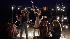 使党靠岸,朋友唱歌和与孟加拉光的舞蹈在电灯泡背景在慢动作的 股票视频