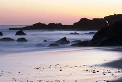 使加利福尼亚峭壁岩石日落靠岸 免版税库存图片