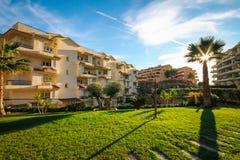 使区域的设计环境美化与棕榈树和生存篱芭的根据家在温暖的秋天太阳和蓝天下在西班牙 免版税库存图片