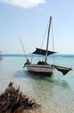 使单桅三角帆船靠岸  库存图片