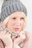 使变冷的白肤金发的妇女佩带的围巾和冬天童帽 图库摄影