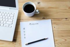 使命膝上型计算机和咖啡的纸清单 免版税库存照片