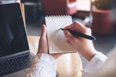 使和写保持向下在有计算机膝上型计算机的一个空白的笔记本的手在桌上 免版税库存图片