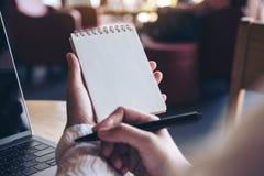 使和写保持向下在有计算机膝上型计算机的一个空白的笔记本的手在桌上 免版税图库摄影