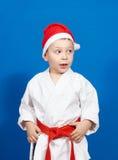 使和服和佩带的圣诞老人帽子的一个小男孩惊奇 库存图片