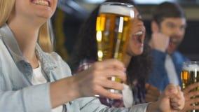 使啤酒叮当响的愉快的爱好者,庆祝喜爱的体育队胜利在客栈 股票录像