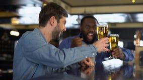 使啤酒杯叮当响的微笑的男性支持者在客栈,庆祝队目标 影视素材