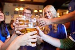 使啤酒杯叮当响的足球迷在娱乐酒吧 免版税库存照片