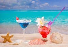 使在加勒比白色沙子的热带红色和蓝色鸡尾酒靠岸 库存照片