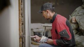 使在墙壁上的建设者膏药光滑使用工具,当工作在站点时 股票视频