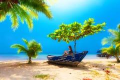 使在掌上型计算机沙子场面夏天树型视图白色的美好的梦想本质靠岸 坐在小船的女孩在棕榈树下 免版税图库摄影
