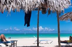 使在梦想海滩与太阳懒人和盖的小屋的风景靠岸在古巴- Serie古巴2016年报告文学 免版税库存照片