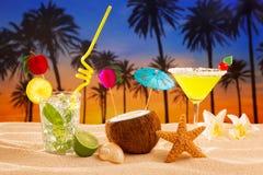 使在棕榈树沙子mojito玛格丽塔酒的鸡尾酒日落靠岸 图库摄影