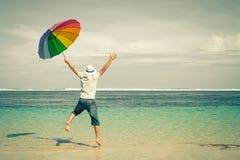 使在沙子海运暑假水的蓝色愉快的跳的人靠岸 沙子海滩 库存图片