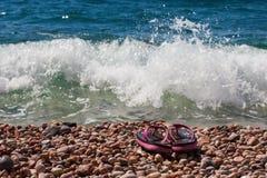 使在海小卵石的鞋子靠岸在波浪 免版税库存照片