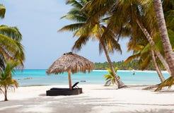 使在白色沙子海滩的遮阳伞靠岸与多云蓝天和太阳 库存图片