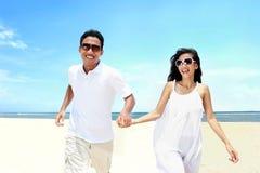 使在运行白色的礼服的夫妇靠岸获得一起笑的乐趣 免版税库存照片