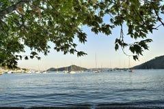 使在费特希耶、土耳其、美好的海滩场面和渔船的看法靠岸 免版税库存照片