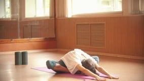 使坐地板兴奋的年轻女人体操运动员在演播室-弯曲对地板-舒展 影视素材