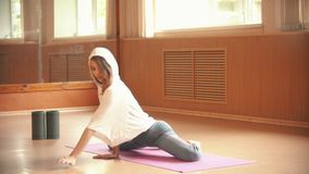 使坐地板和做的年轻女人体操运动员伸展运动兴奋在演播室 股票录像