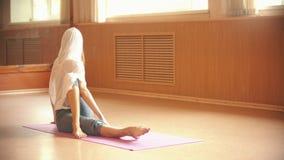 使坐地板和做的年轻女人腿部锻炼兴奋-舞蹈演播室在明亮的白天 影视素材