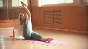 使坐瑜伽席子和做的年轻女人腿伸展运动兴奋-舞蹈演播室 影视素材