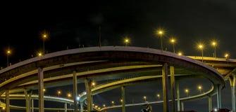 使多云高速公路的夜间和电岗位黄灯复杂化 库存图片