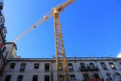 使大厦恢复原状的起重机在里斯本市 免版税图库摄影