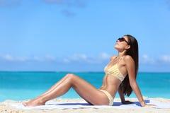 使太阳镜晒黑在性感的比基尼泳装的妇女太阳靠岸 库存图片