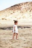 使女孩靠岸走的一点 免版税库存图片