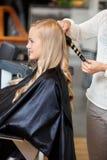 使她的头发的客厅的妇女卷曲 免版税图库摄影