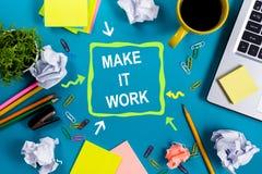 使它工作 办公室有供应的桌书桌,笔记本,杯子,笔,个人计算机,弄皱了纸,在蓝色背景的花 顶层 库存照片