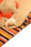 使帽子、明亮的毛巾和贝壳靠岸 库存图片