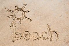 使手写靠岸在海滩的沙子与可爱的太阳的 图库摄影