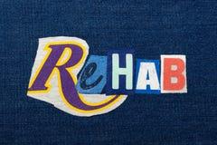 使文本词拼贴画、五颜六色的织品在蓝色牛仔布,修复和补救恢复原状 库存照片