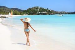 使旅行妇女比基尼泳装佩带的太阳帽子走靠岸 库存图片