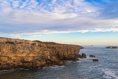 使日落视图环境美化在长袍的海角东贝有门道入口岩石的o 免版税库存照片