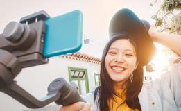 使有智能手机常平架的亚裔妇女录影室外-获得愉快的亚洲的女孩与新技术趋向的乐趣 免版税库存照片