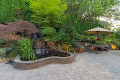 使有瀑布池塘的后院露台环境美化 免版税库存图片