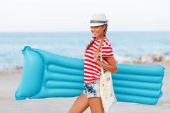 使有蓝色床垫的妇女愉快和佩带的海滩帽子靠岸获得夏天乐趣在旅行假日假期时 免版税库存照片