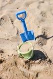 使桶和在沙子困住的海滩铁锹靠岸由孩子 免版税库存图片