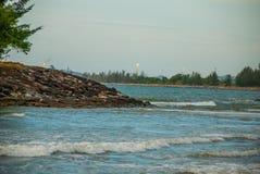 使水的看法环境美化在晚上管子的有在天际的火的,城市民都鲁,婆罗洲,沙捞越,马来西亚 Pantai特马 免版税库存图片