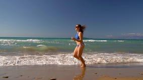 使沿水的比基尼泳装妇女无忧无虑的赛跑靠岸在海滩 科孚岛,希腊美丽如画的沿海  慢的行动 股票录像
