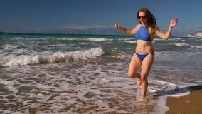 使沿水的比基尼泳装妇女无忧无虑的赛跑靠岸在海滩 科孚岛,希腊美丽如画的沿海  缓慢的概念 影视素材