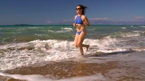 使沿水的比基尼泳装妇女无忧无虑的赛跑靠岸在海滩 科孚岛,希腊美丽如画的沿海  股票录像