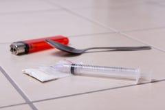 使注射器、海洛因粉末、匙子和打火机服麻醉剂在地板上 免版税库存照片