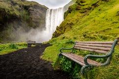 使狂放的Skogafoss瀑布和长凳环境美化看法  免版税图库摄影