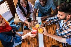 使玻璃叮当响用汁液的小组愉快的朋友在咖啡馆 免版税库存图片